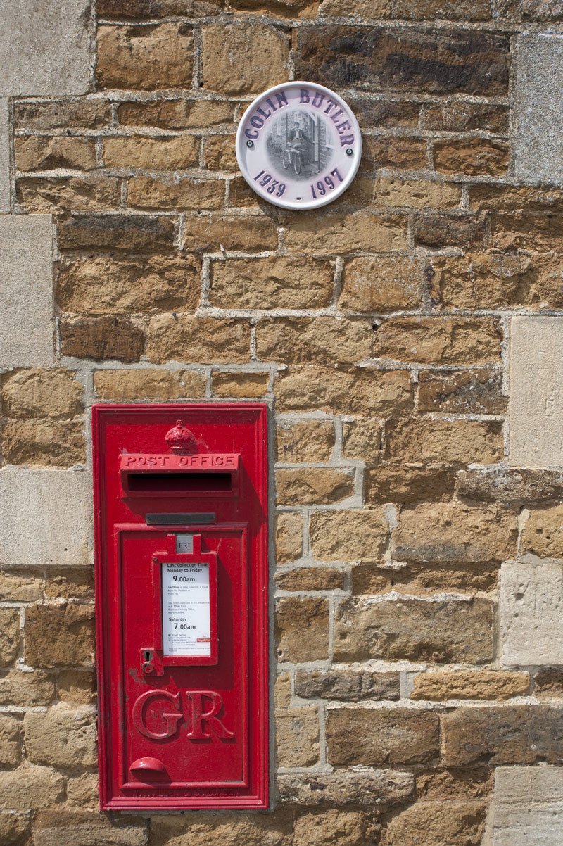 Red village postbox embedded in a wall